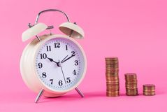 Old clock and golden coins on pink background royalty free stock images