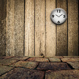 Old clock on grungy wooden wall and brick floor Stock Images