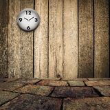 Old clock on grungy wooden wall and brick floor. Old clock on grungy wooden wall and brown brick floor Stock Photography