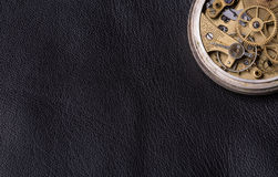 Old clock mechanism on black leather background.  Royalty Free Stock Image