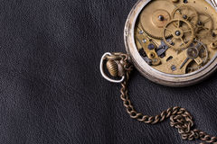 Old clock mechanism on black leather background.  Stock Photo