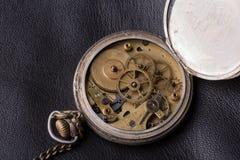 Old clock mechanism on black leather background.  Stock Image