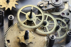 The old clock mechanism with metal gears and screws. Old metal clock unassembled with gears and screws Stock Photos