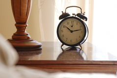 Old clock next to bed Stock Photos