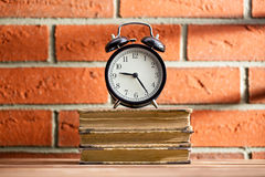 The old clock and old books Stock Photos