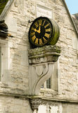 Old Clock on the Outside of a Building. This old clock is positioned high up, on the outside wall, of a parade of shops built in the tudor period. Supported on Royalty Free Stock Image