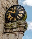 Old Clock on the Outside of a Building. This old clock is positioned high up, on the outside wall, of a parade of shops built in the tudor period. Supported on Royalty Free Stock Photography