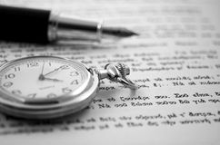 Old clock and a pen. Antique clock with an old pen Royalty Free Stock Photo