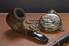 The old clock, the pipe and a pen. A vintage clock together with pipe and pen on a leather plan Royalty Free Stock Image