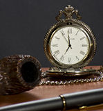 The old clock, pipe, tobacco and pen. A vintage clock together with pipe, tobacco  and pen on a leather plan Stock Photography