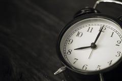 Old clock retro style show 8 o`clock on wood. Background stock photo
