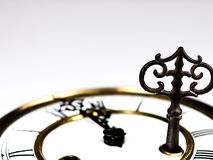 Old clock with roman numerals and key.. Stock Image