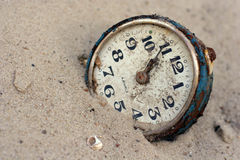 An old clock in the sand Royalty Free Stock Image