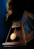 Old clock and a shadowy figure with blue glow Royalty Free Stock Photos