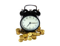 Old clock staying and golden coins. Royalty Free Stock Photo