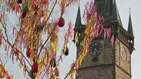 Old clock tower behind the waving Easter fringes. This video shows waving colorful Easter fringes in front of the old Prague clock tower and blue sky. This has stock footage