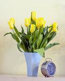 Old clock and tulips. An old, vintage clock standing at the foot of a tulip flowers vase Stock Photos