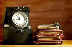 Old clock and vintage books on grunge background Royalty Free Stock Image