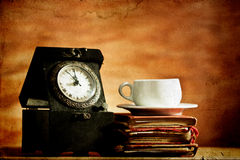 Old clock and vintage books on grunge background Royalty Free Stock Photos