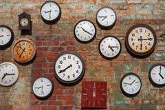 Old clocks. On brick wall stock image