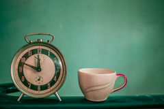 Old clocks and cups of vintage. Stock Images