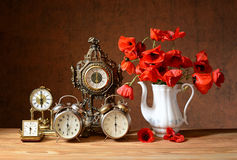 Old clocks and poppies in a vase Royalty Free Stock Photo