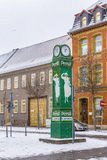 Old clocktower with advertising for washing powder in snow. MUEHLHAUSEN, GERMANY - JAN 17, 2016: old clocktower with advertising for washing powder in snow in Royalty Free Stock Photography