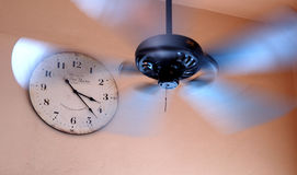Old cloock and a ceiling fan. Old cloock on a wall and a turning ceiling fan royalty free stock images