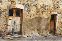 Old closed doors on a cobble stone rock wall Stock Images