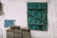 Old closed green window. Destroyed cracked wall. Stacked floor tiles. royalty free stock photography