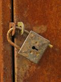 Old closed padlock. On the rusty iron door Stock Photography
