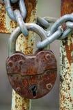 Old closed padlock. On the rusty iron gate Stock Photo