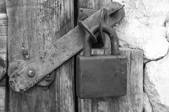 Old wooden door with metalic doorlock. Padlock black and white photo stock photo
