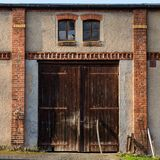 Old closed rustig barn gates in red brick wall. Rural door in sunset light. Stock Photos