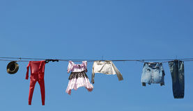 Old Clothes Line. Old clothes hanging on the line against blue sky Royalty Free Stock Image