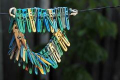 Old clothes pegs hanging on a rope.  Royalty Free Stock Image