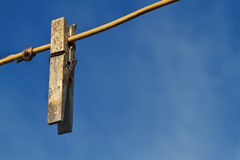Old clothespin on line. An Old weather worn and rusted clothespin on a clothes line against a dark blue sky Stock Photos