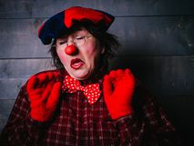 Doubting clown with an anxious facial expression. Old clown in plaid shirt, red gloves and beret with funny facial expressions. Role playing games Stock Image