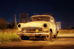 Old clunker in the dark. Old broken car in the street, by night Stock Image