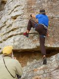 Old coach looks at rock climber Royalty Free Stock Images