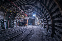 Old coal cart on tracks in mine. Fisheye view of coal cart located in bended corridor in modern coal mine, tracks and elements of internal infrastructure visible stock image
