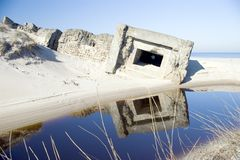 Old coastal military bunker. Scenic view of old coastal military bunker reflecting in water, beach and sea in background Stock Photos