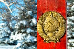 The old coat of arms of the USSR against the red pillar which stands in the woods. In the winter on the border stock photos