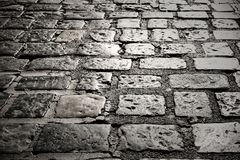 Old cobble stone road surface paving dark night background textu Stock Image
