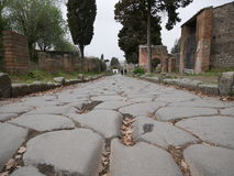 Old cobbled path in Pompeii. Low angle view looking along an old cobbled path in Pompeii, Italy with historic ruined buildings on either side and small people in Royalty Free Stock Photo
