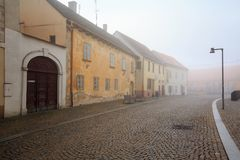 Old cobbled street in the historical downtown on a foggy winter day. Znojmo, Czech Republic. ZNOJMO, CZECH REPUBLIC - DECEMBER 28, 2017. Old cobbled street in Royalty Free Stock Image