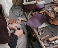 Cobbler while repairing the shoe with a piece of leather. Old cobbler while repairing the shoe with a piece of leather stock photos