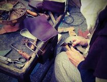 Old cobbler while repairing the shoe with a piece of leather wit. Cobbler repairs the shoes with a piece of leather with vintage effect stock photography