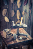 Old cobbler workplace with shoes, laces and tools Royalty Free Stock Images