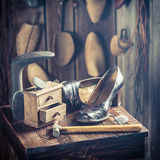 Old cobbler workplace with tools, shoes and laces Royalty Free Stock Photos